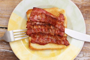Crispy bacon on toast on plate, closeup