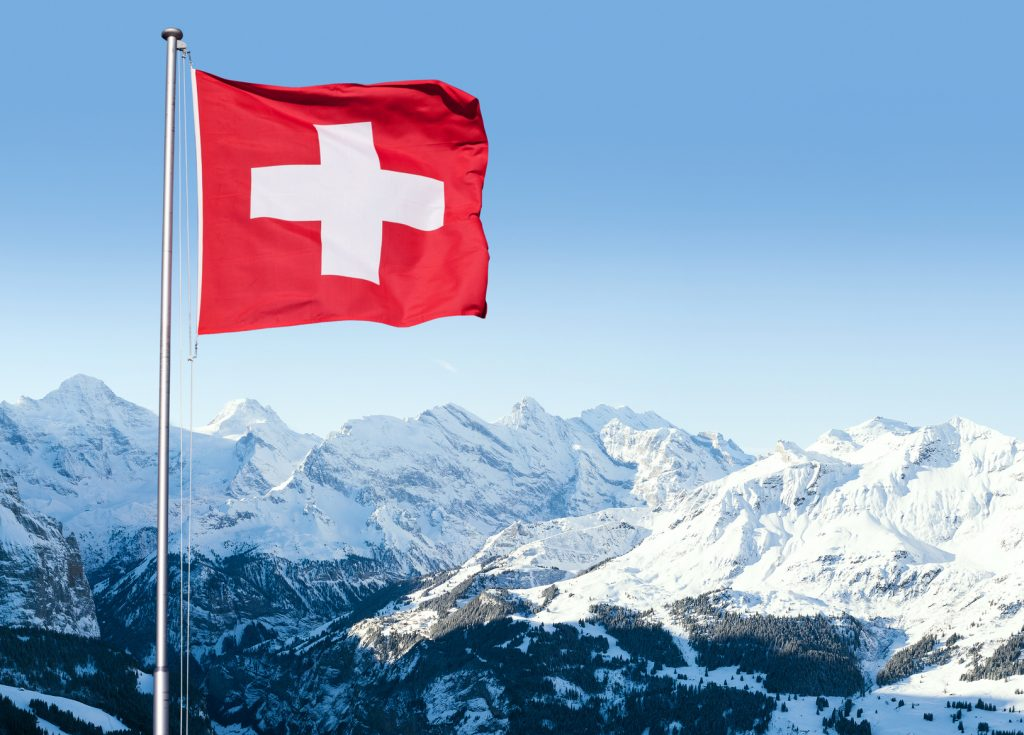 The flag of Switzerland fluttering in the wind with the Bernese Alps in the background, Grindelwald, Switzerland.