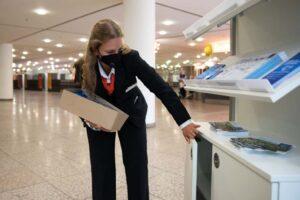 Hallenläuferin beim Auffüllen von Info-Material